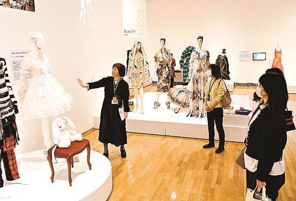 南目美輝学芸課長(左)からロリータファッションについて説明を聞く参加者=益田市有明町、島根県立石見美術館